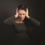 Stressed unhappy business woman closed ears the hands because not want the hear any sounds and noise on dark grey background