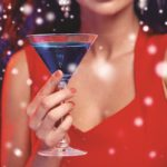 people, winter holidays, party, alcohol and leisure concept - close up of beautiful sexy woman in red dress with cocktail glass at nightclub over snow