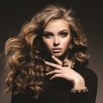 Beautiful woman with long curly hair and gold jewelry posing at studio