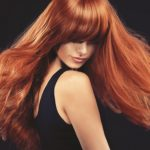 Beautiful model girl  with long red curly hair . Hairstyle and